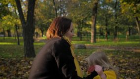 Carefree child, joyful smiling female child hugs her loving mother tightly while walking in autumn park in fall season