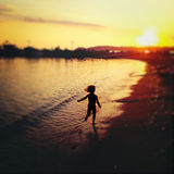 Carefree child running on beach. At sunset Royalty Free Stock Photos