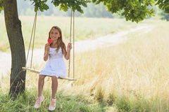 Carefree child swinging with candy. Pretty girl is eating lollipop with enjoyment. She is sitting on swing in meadow. Kid is smiling Royalty Free Stock Photo