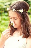 Carefree childhood. Girl with butterfly smelling camomile . Royalty Free Stock Photo