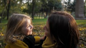 Carefree childhood, smiling girl joyfully runs to her loving mother during a walk in autumn park, concept of happiness
