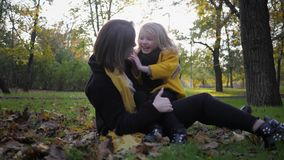 Carefree childhood, young attractive female mother sits on lawn with her charming smiling daughter while walking in