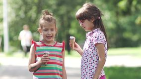 Carefree children eat ice cream in summer Park. two little girls having fun talking and smiling stock video footage
