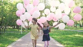 Carefree children are happy with the balloons that their parents gave them. Little girls enjoy a warm sunny summer day. Children run through the Park with a huge stock footage