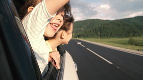 Carefree children leaned out the car window and smiling. two little girls having fun in car. slow motion stock footage
