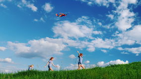 Carefree children play with a kite. Running along the green hill against the blue sky with white clouds. Happy childhood stock video