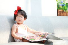 Carefree Chinese baby girl hold a menu on sofa. Cute Asian Chinese baby girl in red bow on her head, wears white dress, play in a garden, innocent little girl Royalty Free Stock Image