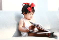 Carefree Chinese baby girl looks at menu on a sofa Stock Photo