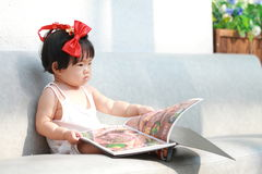 Carefree Chinese baby girl looks at menu on a sofa. Cute Asian Chinese baby girl in red bow on her head, wears white dress, play in a garden, innocent little Stock Photo