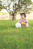 Carefree Chinese baby girl play a ball and balloon on the lawn Stock Photo