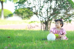 Carefree Chinese baby girl play a ball and balloon on the lawn. Carefree Chinese little baby girl, sit on a lawn, play with leaves, enjoy free time, embrace Stock Photos