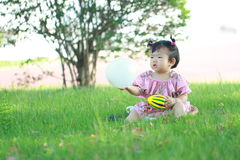 Carefree Chinese baby girl play a ball and balloon on the lawn. Carefree Chinese little baby girl, sit on a lawn, play with leaves, enjoy free time, embrace Stock Images