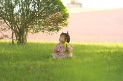 Carefree Chinese baby girl play a ball on the lawn Royalty Free Stock Image