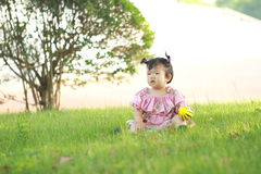 Carefree Chinese baby girl play a ball on the lawn Royalty Free Stock Images