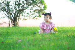 Carefree Chinese baby girl play a ball on the lawn Stock Photos