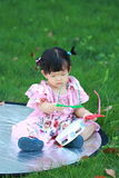 Carefree Chinese baby girl play on the lawn Royalty Free Stock Image