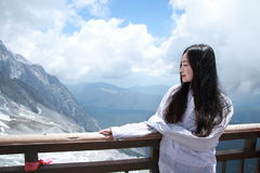Carefree Chinese beauty look towards on Jade dragon snow mountain. Chinese girl climb Jade dragon snow mountain at Yunnan province, it is a very famous snow royalty free stock photos
