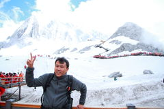 Carefree Chinese man on Yunnan Jade dragon snow mountain,A gesture of victory. Chinese man climb Jade dragon snow mountain at Yunnan province, it is a very royalty free stock photo
