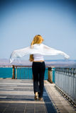Carefree concept - back of blond woman on bridge Royalty Free Stock Images