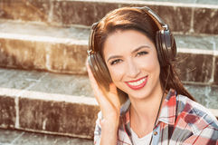 Carefree concept with beautiful woman smiling and listening musi. C on headphones outside in the park royalty free stock photo