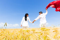 Carefree couple. Carefree field running spring love couple with red tissue scarf Stock Photography