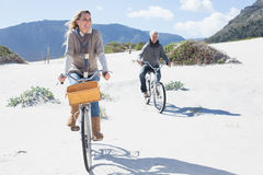 Carefree couple going on a bike ride on the beach Royalty Free Stock Photography