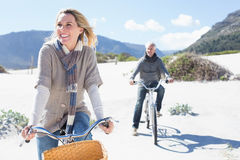 Carefree couple going on a bike ride on the beach Stock Image