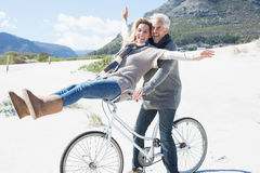 Carefree couple going on a bike ride on the beach Royalty Free Stock Photos