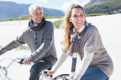 Carefree couple going on a bike ride on the beach Stock Photos