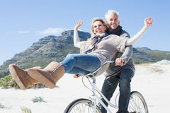 Carefree couple going on a bike ride on the beach Stock Images