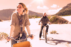 Carefree couple going on a bike ride on the beach. On a bright but cool day Royalty Free Stock Photos