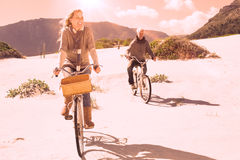Carefree couple going on a bike ride on the beach. On a bright but cool day Royalty Free Stock Photography