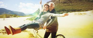 Carefree couple going on a bike ride on the beach. On a bright but cool day Stock Photos