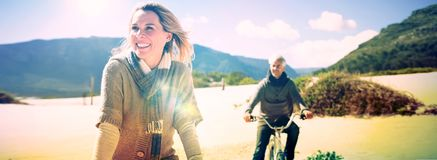 Carefree couple going on a bike ride on the beach. On a bright but cool day Stock Image