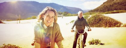 Carefree couple going on a bike ride on the beach. On a bright but cool day Stock Photo