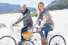 Carefree couple going on a bike ride on the beach smiling at camera Royalty Free Stock Photos