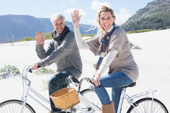 Carefree couple going on a bike ride on the beach waving at camera Stock Photo