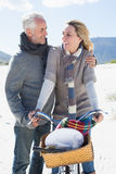 Carefree couple going on a bike ride and picnic on the beach Stock Photos