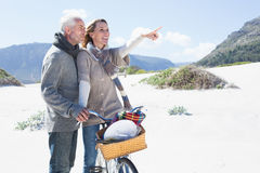 Carefree couple going on a bike ride and picnic on the beach Royalty Free Stock Photos