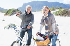 Carefree couple going on a bike ride and picnic on the beach Stock Photo