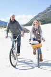 Carefree couple going for a bike ride and picnic on the beach Stock Photography