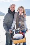 Carefree couple going on a bike ride and picnic on the beach Stock Images