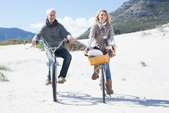 Carefree couple going for a bike ride and picnic on the beach Stock Images