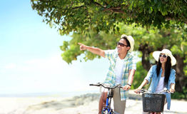 Carefree couple having fun and smiling riding bicycle at the bea. Portrait of carefree couple having fun and smiling riding bicycle at the beach Royalty Free Stock Images