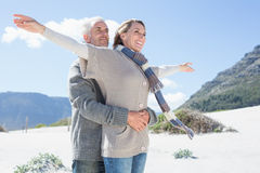 Carefree couple hugging on the beach in warm clothing Royalty Free Stock Photos