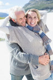 Carefree couple hugging on the beach in warm clothing Stock Images