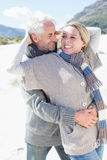 Carefree couple hugging on the beach in warm clothing Stock Image
