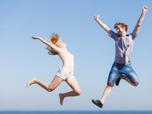 Carefree couple jumping against blue sky Royalty Free Stock Photography