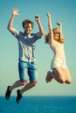 Carefree couple jumping by sea ocean water. Royalty Free Stock Image