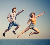 Carefree couple jumping by sea ocean water. Stock Photography
